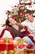 Image details Young couple sitting together in front of Christmas tree