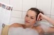 Dettagli della fotografia Body care series - Young woman with magazine in the bathtub