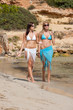 Dettagli della fotografia Two attractive woman walking on the beach