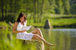 Details der Fotografie Happy romantic woman sitting by lake with book