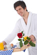 Details der Fotografie Breakfast - young man holding tray with rose