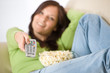 A fényképek részletei Woman watching television with popcorn in living room
