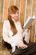 Dettagli della fotografia Young romantic woman in barn reading book