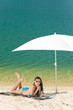 Details der Fotografie Summer beach woman blue bikini under parasol