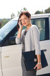 Detalii fotografie Elegant businesswoman stand by luxury car calling