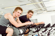 Image details Fitness young man on gym bike spinning