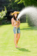 Details der Fotografie Summer garden woman play with water hose