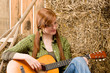 Detalii fotografie Young country woman playing guitar in barn