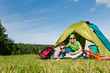 Details der Fotografie Camping couple lying inside tent summer countryside