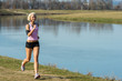 Details der Fotografie Young woman jogging by sunny river bank