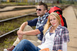 Dettagli della fotografia Couple backpack traveling resting on railroad trip