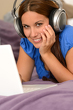 Detalii fotografie Young smiling girl using laptop with headphones
