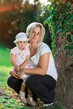 Details der Fotografie young pregnant woman with baby girl at summer garden