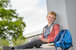 Image details Happy boy studying sitting on wall campus