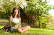 Dettagli della fotografia Student girl reading book sitting on grass