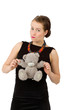 A fényképek részletei attractive smiling brunette holding teddy bear grimacing with peg on nose in a black dress isolated on white