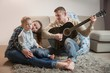 Details der Fotografie happy family father playing guitar at home