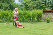 Detalii fotografie woman mows the grass in the garden with an electric lawnmower