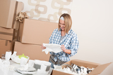 Moving house: Happy woman unpacking dishes