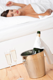 Champagne in ice bucket, woman sleeping in background