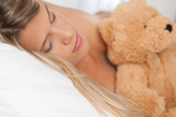 White lounge - Sleeping woman holding brown teddy bear