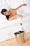 Naked woman in white bed with champagne