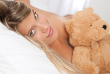 White lounge - Blond woman lying in bed with teddy bear