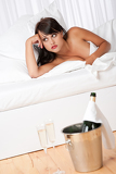 Sexy naked woman in white bed with champagne
