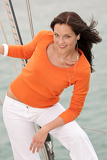 Fotografia Attractive woman standing on sailing boat with headphones