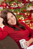 Brown hair woman relaxing in front of Christmas tree