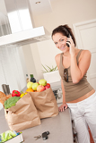 Young smiling woman with groceries in the kitchen