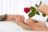 Fényképek White lounge - Beautiful woman lying in white bed holding red rose