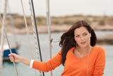 Attractive woman standing on sailing boat with headphones