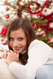 Smiling young woman in front of Christmas tree