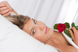 White lounge - Beautiful woman lying in bed holding red rose