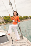 Young woman standing on sailing boat with cup of coffee
