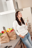 Young woman with groceries in the kitchen