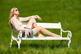 Fotografie Spring - Young woman relaxing on bench in meadow