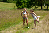 Two young women exercising in a meadow