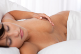 Young woman lying naked in white bed