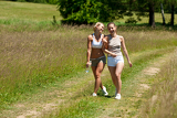 Female couple walking in meadow