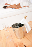 Bottle of champagne in ice bucket, naked woman in background