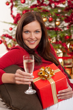 Smiling woman with Christmas present and glass of champagne