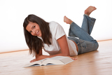 Happy teenager lying down with book