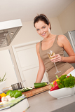 Smiling young woman cooking in the kitchen