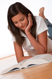 Teenager reading book lying down