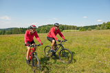 Photo Young couple riding mountain bike in spring meadow