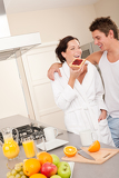 Young man and woman eating toast in the kitchen