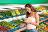 Grocery store shopping - Woman holding mobile phone