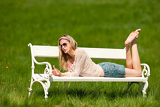 Spring - Young woman relaxing on bench in meadow